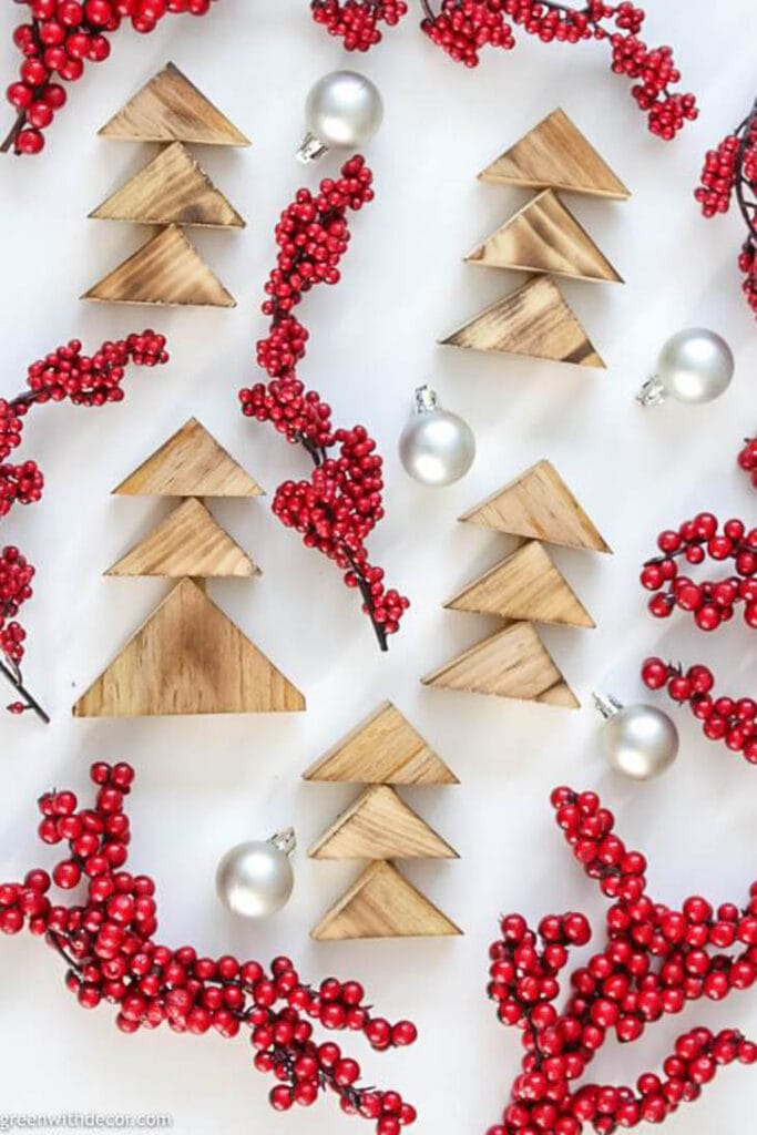 Scrap wood triangles put together as Christmas trees laying with red berry twigs and silver ornaments
