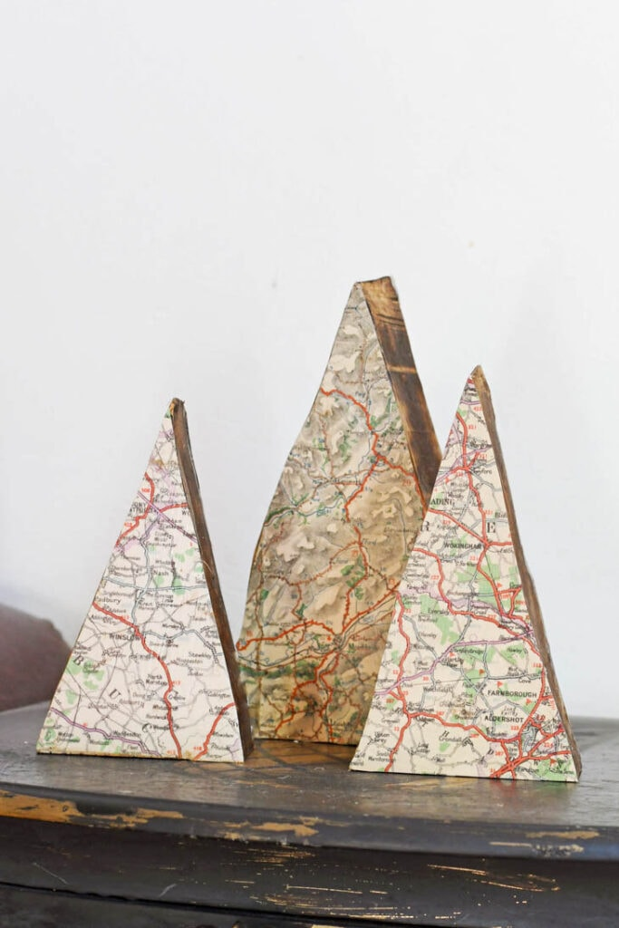 Triangle shaped scrap wood as Christmas trees with maps decoupaged onto them
