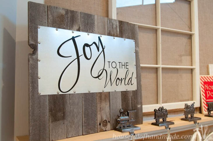Joy to the world on metal mounted on scrap wood