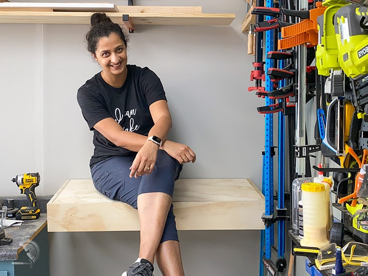 Woman sitting on floating shelf to test how strong it is