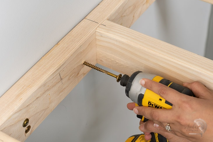 Attaching the floating shelf to the wall using a screw