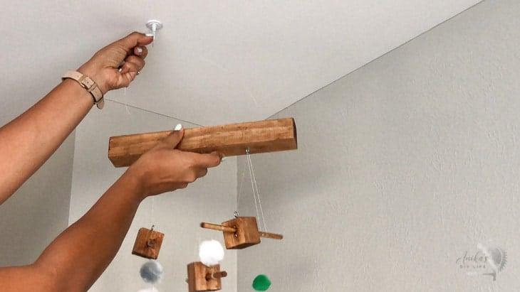 Woman hanging up DIY animal mobile