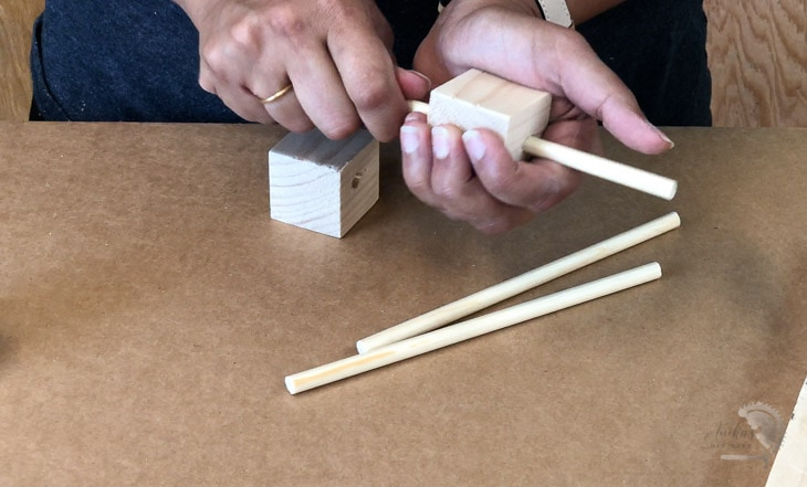 Adding the dowels through the cubes to make the DIY woodland mobile