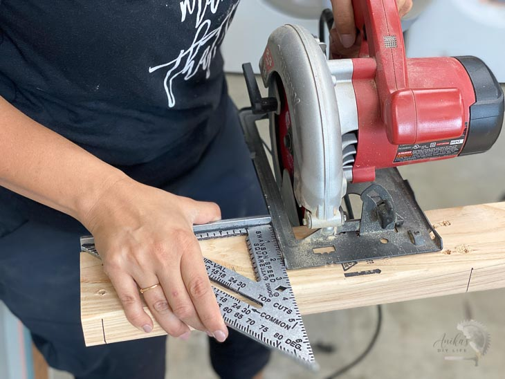 Woman cutting a board with a circular saw using a speed square as a guide.
