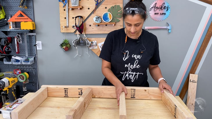 woman putting together 2x4 to build the floating shelf