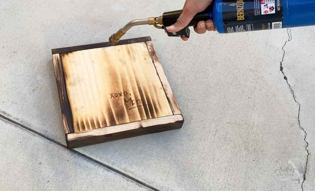 Using a blow torch to show message written with scorch marker.