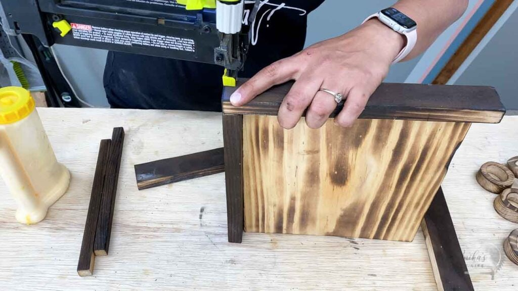 Attaching the boards to make a tic tac toe board using a brad nailer