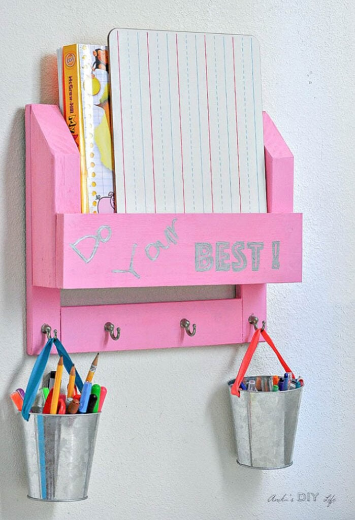 Pink DIY desk organizer with aluminum pails hanging from the hooks with pencils and crayons