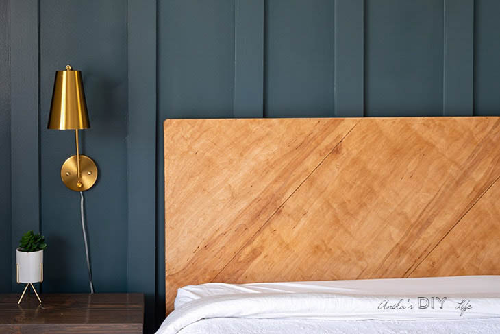 plywood headboard against board and batten dark painted board and batten wall