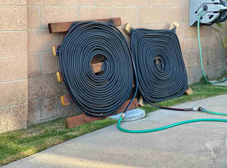 Two homemade solar pool heater coils next to a pool