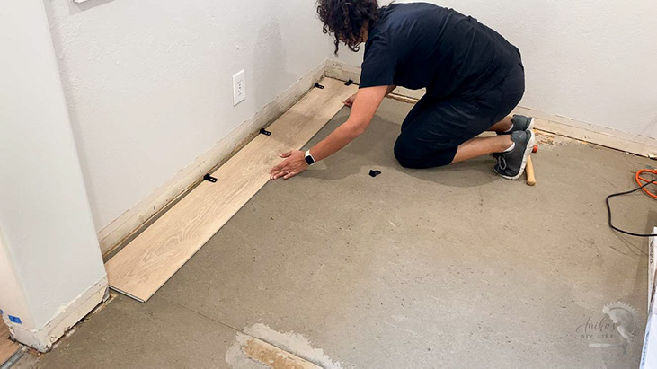 Woman installing the first row of vinyl plank flooring