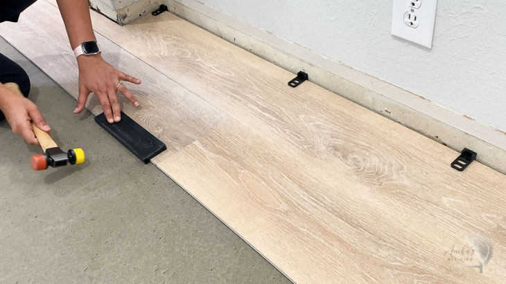 Woman tapping in the second plank of vinyl plank flooring