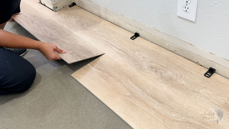 woman installing second plank of the vinyl plank flooring