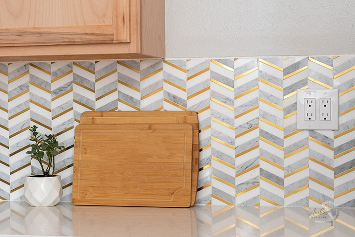 herringbone backsplash tile with gold and marble in the kitchen