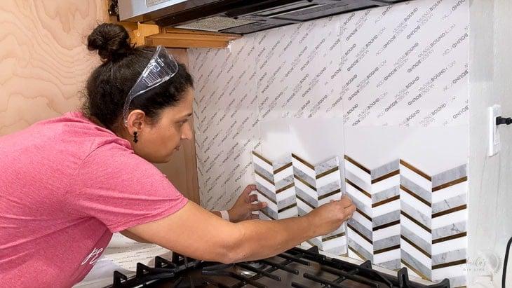 woman applying tile to the adhesive tile mat