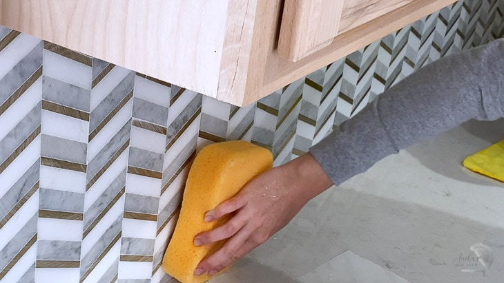 wiping down grout using a damp sponge
