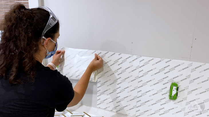 woman applying the Musselbound adhesive tile mat to the wall