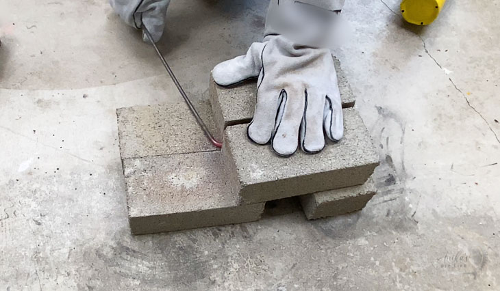 Bending steel rod around a cement brick