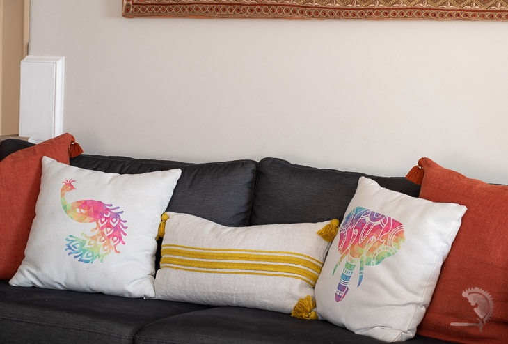 colorful pillows with peacock and elephant on couch