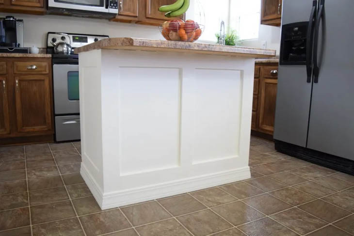 small white island with trim molding and basket of fruit sitting on the countertop