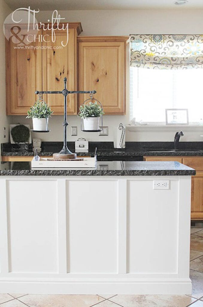 kitchen island with board and batten trim painted white with black stone countertop