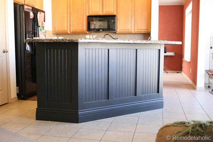 black kitchen island with beadboard framed with wood trim