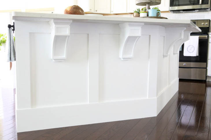 white kitchen island with wood trim and corbels under the countertop