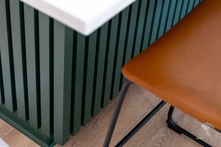 close up of dark green kitchen island with brown counter chairs