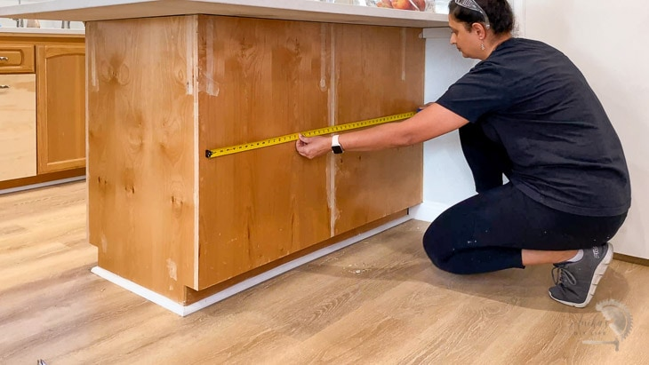 Woman measuring the kitchen island to calculate trim
