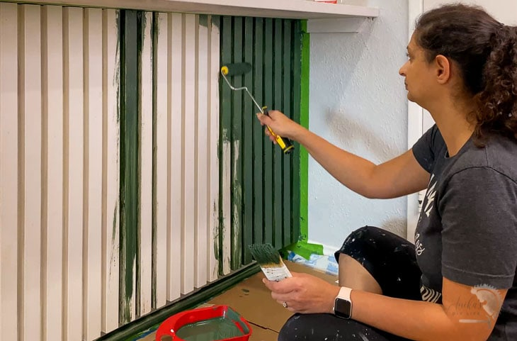 Woman painting the slat kitchen island with green paint