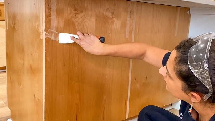 Woman filling nail holes in Island to prepare for trim