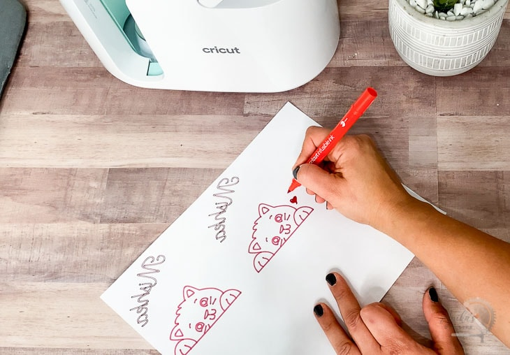 woman hand drawing designs on laser copy paper for Cricut MugPress