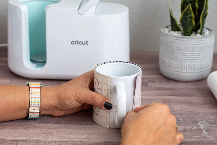 Woman aligning design to mug to use in the Cricut MugPress