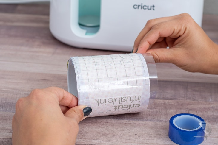 Woman applying tape to the design for the Cricut Mugpress