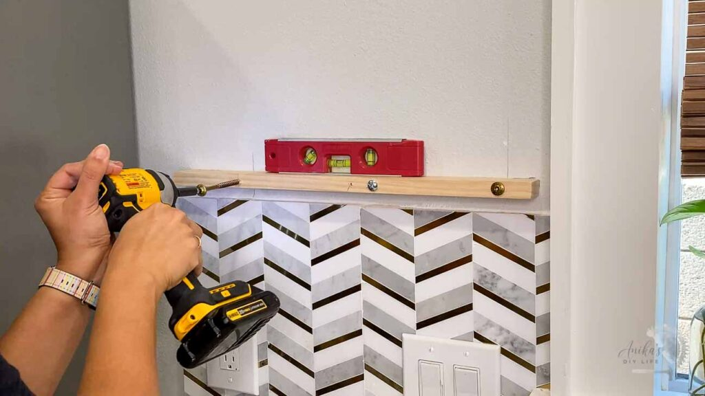 woman using  structureal screws to attach board to wall.