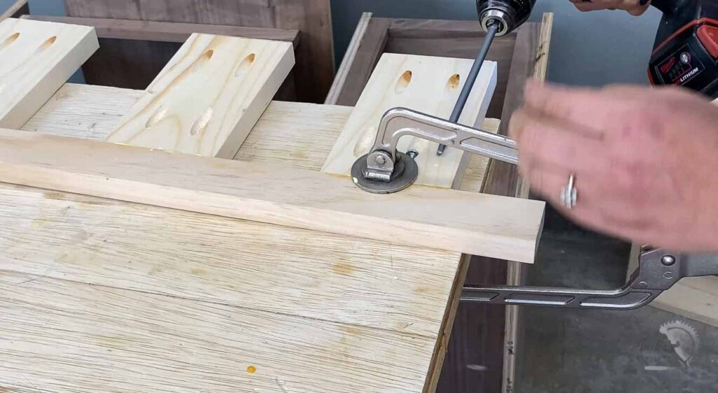 Woman building the brace for the floating shelves using pocket holes