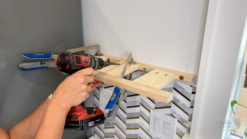 Woman attaching the brace to the wall using pocket hole screws for a floating shelf in the kitchen
