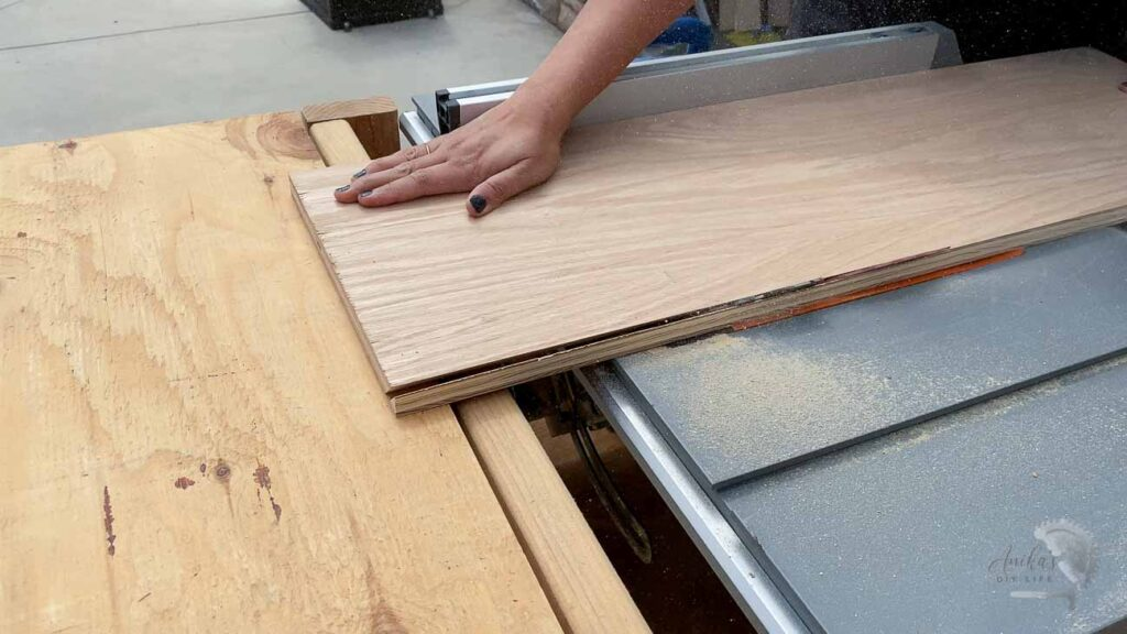 Woman cutting plywood on table saw to build kitchen shelves