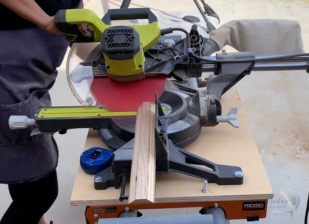 Woman cutting the floating shelves on a miter saw