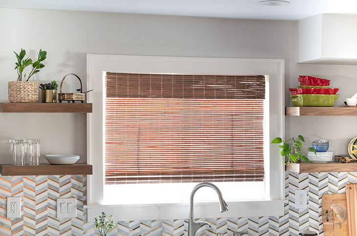 DIY wood floating shelves on both sides of a window in a kitchen