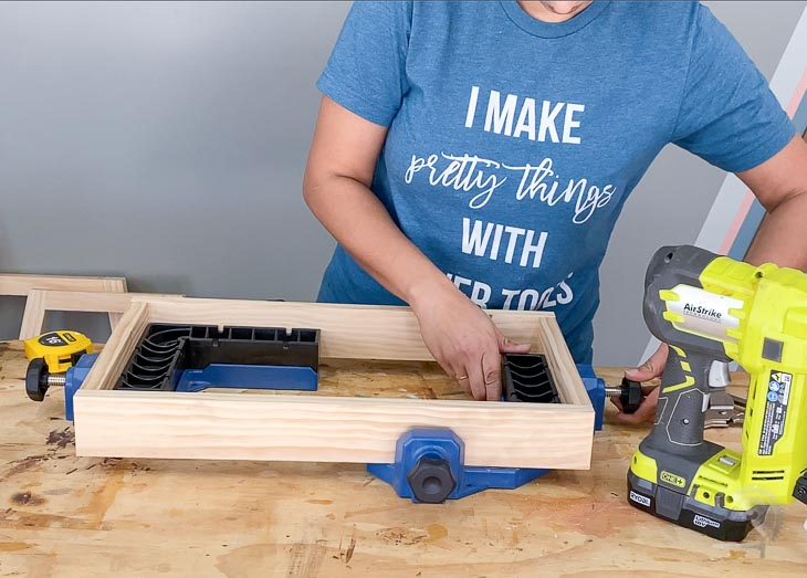 woman building a small square box using clamps
