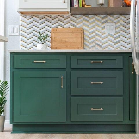 Green kitchen cabinnets with tile backsplash