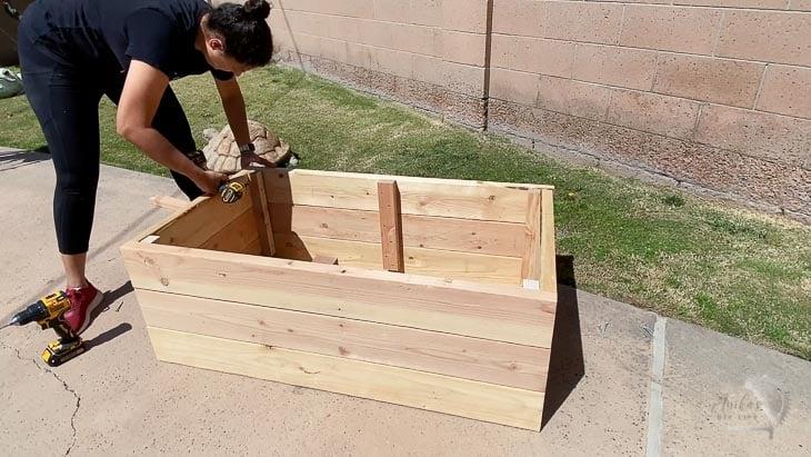 woman building a planter box in backyard