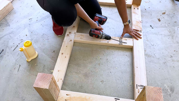 woman building the base of the self-watering planter on a garage floor