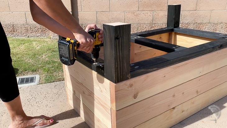 woman attaching the legs to the self-watering planter box