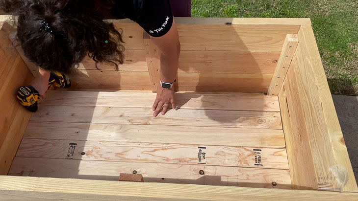 adding the 2x4 slats to the bottom of the DIY planter