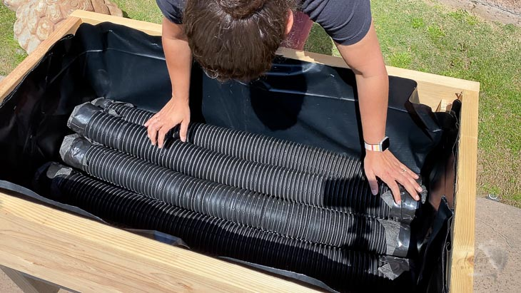 woman laying the corrugated perforated pipes inside the planter to make the DIY self watering raised garden bed