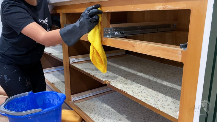 Woman cleaning cabinet with TSP to prepare for painting