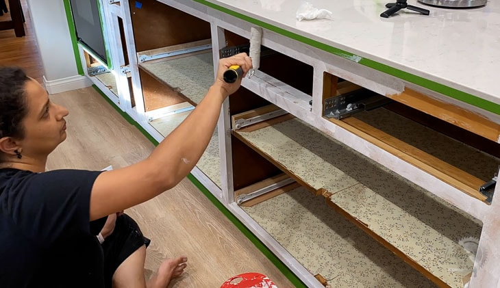 Woman applying primer to kitchen cabinet