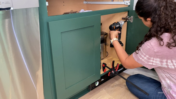 Woman installing kitchen cabinet doors